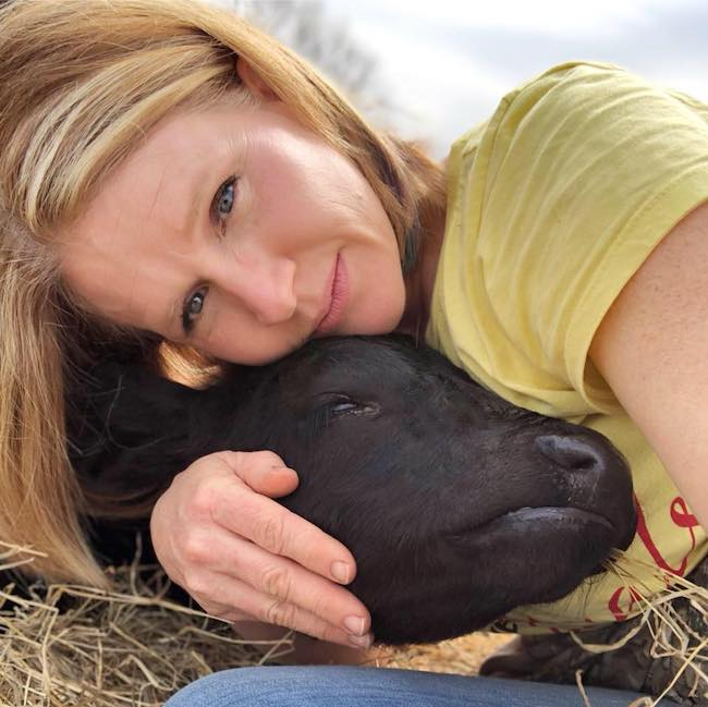woman hugging baby calf