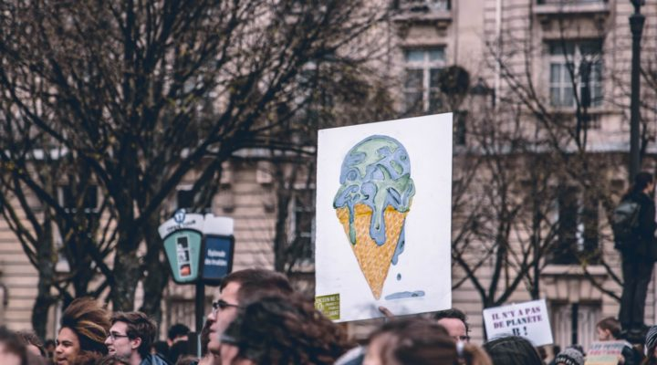 a protest sign with the earth as an ice-cream cone melting